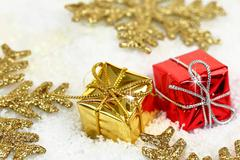 Two Christmas gift boxes with gold snowflakes on snow - stock photo