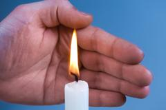 Hands Kindle candle Stock Photos