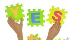 "Hands forming word ""Yes"" with jigsaw puzzle pieces - stock photo"