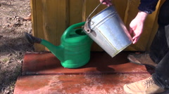 Gardener in farm pour water in plastic watering can Stock Footage