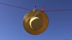 clothes line with woman straw summer hat in wind and sky - stock footage