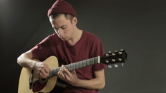 Young musician playing guitar in dark studio Stock Footage