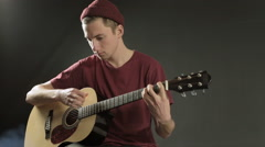 Talented young musician playing guitar in a dark studio in smoke Stock Footage