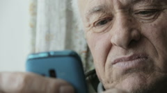 Old man using new technology: mobile phone, cell phone, smartphone Stock Footage