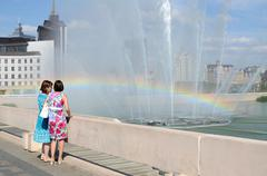 Two women admire a rainbow in the fountain in the lake Bottom Boar, Kazan - stock photo