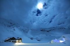 Night Sky With Old Wood Cabin and Ice Hotel in winter scene Stock Photos