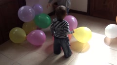 Calm baby watches a crazy one playing with balls Stock Footage