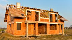 Rough brick building house under construction - stock photo