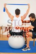 Composite image of man on yoga ball working with a physical therapist Piirros