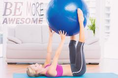 Stock Illustration of Composite image of cheerful fit blonde holding exercise ball between legs