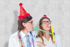 Stock Photo of Composite image of geeky hipster wearing a party hat with blowing party horn