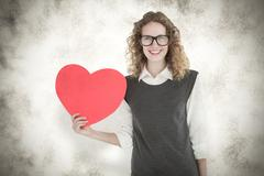 Composite image of geeky hipster holding heart card - stock photo
