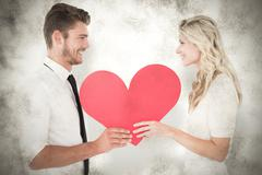 Composite image of attractive young couple holding red heart Stock Photos