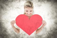 Composite image of attractive young blonde showing red heart Stock Photos