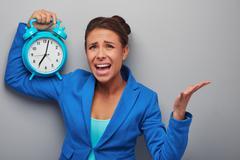 Awaken mixed race woman with alarm clock - stock photo