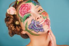 Close up portrait of woman model with hand drawing flowers on her face - stock photo