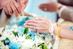 hand of a bride receiving holy water from elders in thai culture - stock photo
