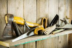 Many old tools ( axe, saw and others) on a wooden shelf. - stock photo