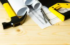 Drawings for building and working tools on wooden background. - stock photo
