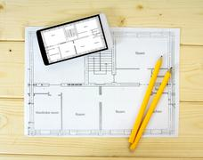Tablet, drawings and pencils on a wooden background. - stock photo