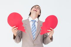 Geeky businessman crying and holding broken heart card Stock Photos