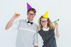 Stock Photo of Geeky couple with party hat and party horn