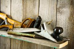 Many old tools ( axe, saw and others) on a wooden shelf. Stock Photos
