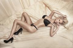 Sexy blonde woman lying on bed. Stock Photos