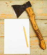 Paper with pencil and axe on wooden background. Stock Photos