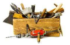 Working tools (drill, axe, saw and others) in an old box on white background. - stock photo