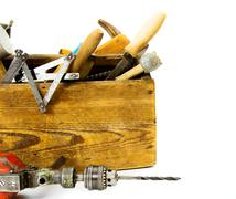 Working tools (drill, axe, saw and others) in an old box on white background. Stock Photos