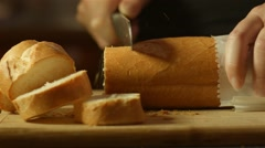 Fresh golden brown bread cutting up in kitchen on bread board Stock Footage
