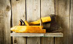 Many old tools (axe, plane and others) on a wooden shelf. - stock photo