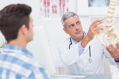 Doctor explaining anatomical spine to his patient - stock photo