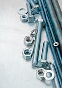 Metal hairpins and bolts on the scratched metal background. - stock photo