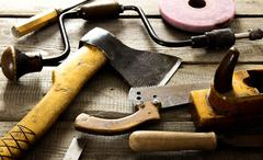 Many old working tools ( axe, saw and others) on a wooden background. Stock Photos