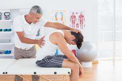 Doctor stretching a young man back Stock Photos