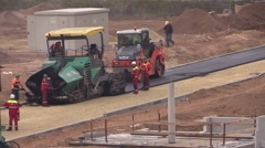 Workers spread and roll machines lay asphalt in flat district Stock Footage