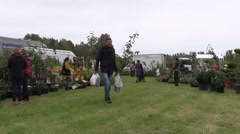 People buy flowers and plants in botanical garden market fair Stock Footage