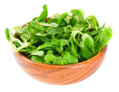 Greens on wooden bowl. - stock photo