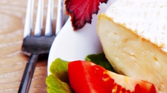 Brie cheese on salad in white dish Stock Footage