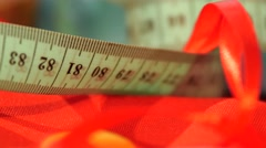 Measuring tape isolated on red cloth, close up Stock Footage
