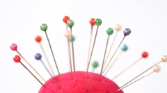 Varicolored needles are stocking on the top of pincushion, close up Stock Footage