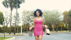 Sexy Ethnic woman walking towards camera with shopping bags Stock Footage