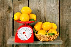 Lemons on scales and in a basket Stock Photos