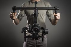 Professional videographer with gimball video slr - stock photo