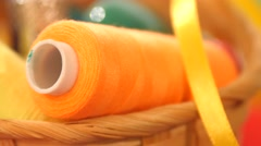 Yellow bobbin of thread with ribbon in the basket, close up Stock Footage