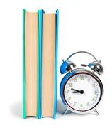 Alarm clock and multi-coloured books. Stock Photos