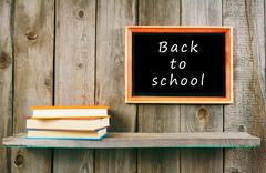 Back to school. Books on wooden shelf and frame. - stock photo