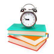Alarm clock and multi-coloured books. - stock photo